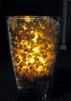 Simply place a small vase within a larger one, and fill in the space between the two with popcorn. Light candle in middle vase.