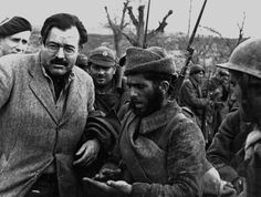 Teruel, Spain. US writer and journalist Ernest Hemingway with soldiers at the front lines by Robert Capa, (December-1937)
