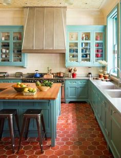 love the color combo...the teal cabinets...the terracotta floor tiles....the range hood...the openiness of cabinets...the butcher blcok island...