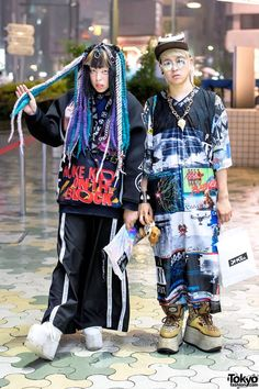 "Shoushi(left) 18, fashion student. He's wearing a DVMVGE (Damage) ""Nuke Kids on the Block"" sweatshirt with M.Y.O.B NYC pants, and YRU platform shoes. Accessories: harnesses from Devilish and DVMVGE as well as holographic clutch by DVMVGE. Yana(right) 22, and works in the apparel industry. He's wearing a graphic setup from DVMVGE with Buffalo platform boots. Yana's bone cap, skull necklace, and animal skulls bracelet are all from OS Accessories, his bag is Jeremy Scott."