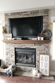 Don't like the arrow like shape of the mantle. Beautiful stacked stone fireplace with Fall decorated mantle