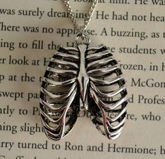 jewels necklace ribs skeleton grunge jewelry<<< I love the necklace but the back round is a page from harry potter Cute Jewelry, Jewelry Box, Jewelery, Jewelry Accessories, Jewelry Necklaces, Jewelry Design, Jewelry Gifts, Silver Necklaces, Druzy Jewelry