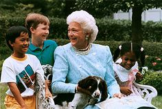 First Lady Barbara Bush, with her dog Millie, reading a story to children.