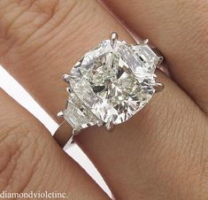 A Breathtaking Estate HANDMADE PLATINUM (stamped) Diamond Three-Stone Engagement ring dazzles GIA Certified 4.00ct Cushion Center Diamond in N color SI2 clarity (Very Bright, warm tint and eye clear) with measurements of 9.36x8.54x6.10mm. It is set with 2 Large Step cut Trapezoid shaped