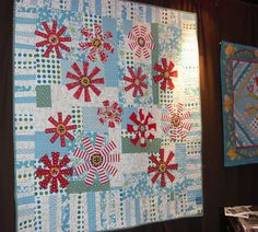 Scrappy aqua, green, and white background with large red asterisk-star-flowers. Interesting quilt!