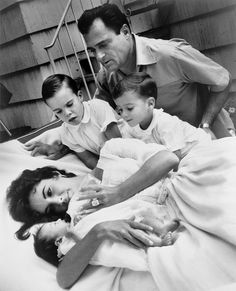 Elizabeth Taylor bottle feeding newborn Liza Todd with her sons Christopher and Michael H Wilding, and her husband Michael Todd observing