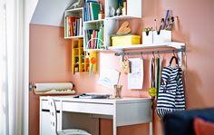 Et hjørne til at lave lektier i stuen med et skrivebord, en stol og vægskabe fra IKEA.