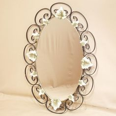 Rustic wall mirror decorated with wrought iron leaf designs.