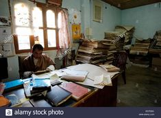 Piles of handmade papers at the office of a workshop which produces traditional Bhutanese paper handmade from Daphne bush in the city of Thimpu in Bhutan Stock Photo Paper Factory, Waterford City, The Ca, Two Trees, Prayer Book, Bhutan, The Office, Natural Light, Workshop