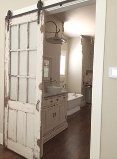 Old chippy distressed door turned barn door style setup...with matching colored vanity.