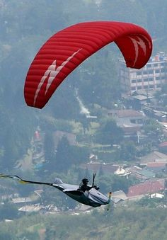 An Indonesian paraglider flies during a paragliding festival over Puncak, near Bogor, Indonesia