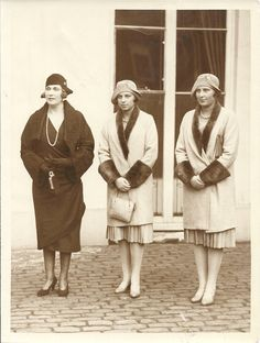 """Queen Ena and her two daughters, Beatriz & Maria Cristina, wearing matching coats (Marlene A. Eilers Koenig collection)    Queen Victoria Eugenia has always """"followed the Spanish custom of dressing daughters of the same approximate age as twins."""" She has made arrangements """"with their old shops for noble proxies to obtain dresses"""" and send them to Fontainebleau, where the Queen and her daughters now live."""