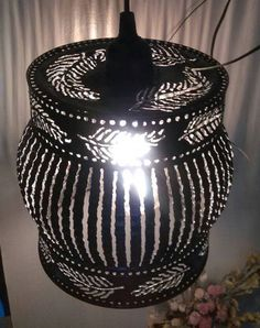 This pendant light in a floating feather pattern adds a touch of grace and whimsy! I use an oxyacetylene welding torch to cut the patterns into this gallon sized tin can.    Hang alone or in groupings for impact or over a work space for great lighting.    -Measures 8 inches wide by 6 inches high.    -Comes ready to hang with a vintage style Edison bulb. Choose option of 11 foot black cord plug in style, or a hard wire set up complete with 4 feet of black vintage twisted cloth wire and…