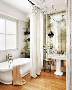 tub, curtain, wood floors, sink, window above tub, faucets, flowers next to sink,shelves on wall behind curtain, colors