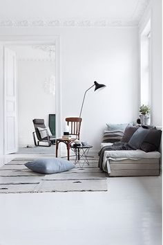 grey decor white walls and flooring throws scatter cushions lamp stand wooden chair high ceilings