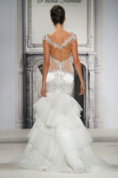 Pnina Tornai fit and flare wedding dress with crystal cap sleeves, open illusion back, silk satin bodice, dropped waist, tiered tulle and satin skirt, and sweep train.