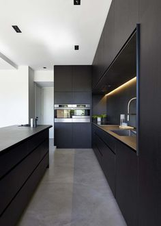 kitchen idea - M House is a minimalist house located in Melbourne, Australia, designed by DKO. The kitchen space features blacked out custom cabinetry with a black kitchen island that allows for seating and serving. Kitchen Decorating, Home Decor Kitchen, Kitchen Furniture, New Kitchen, Kitchen Ideas, Kitchen Inspiration, Awesome Kitchen, Kitchen Layout, Concrete Furniture