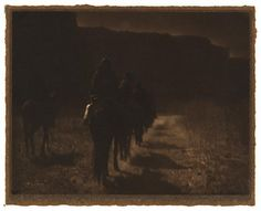 Navajos on horseback, circa 1904, by Edward S.Curtis, Platinum print.  The print is very dark.  They are riding in a line.