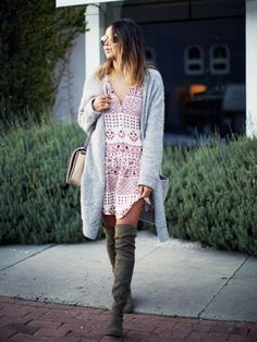 Julie Sarinana of Sincerely Jules wearing olive green over-the-knee boots with a long cardigan layered over a printed dress
