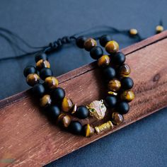 Tigers Eye is a set of men's bracelets made with natural tigers eye beads and matte black agate beads. Tigers eye helps focus the mind to face difficult setbacks, while both the tigers eye and black agate provide protection, courage, strength and grounding. The bracelets also features a gold tiger head charm which represents power and the ability to overcome obstacles, the tiger head charm features clear and green cubic zirconias. Both bracelets are made with adjustable sliding knot…