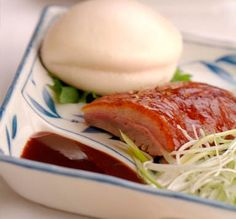 PEKING DUCK  A Yank Sing Signature dish. Crispy paper-thin honey-coated skin and tender slices of succulent house-roasted Peking Duck, stuffed in a steamed seashell bun, accompanied with finely slivered scallions and tangy hoisin sauce.