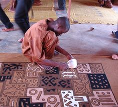 """This large, 46""""W x 72""""L blanket is handmade artisans in Bamako, Mali who grow and weave local cotton. The artisans use an updated mud cloth technique to create abstract, geometric patterns. Each blanket is hand-dyed and one-of-a-kind."""