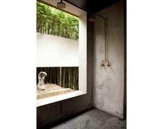De frente para o jardim e para uma escultura, este banheiro conta com chuveiro de estilo antigo, triplo, e cimento queimado