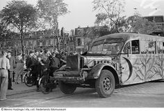 Retreat of German soldiers after their surrender in an advanced and camouflaged bus, checked by residents and allied soldiers, The Hague (May 1945)