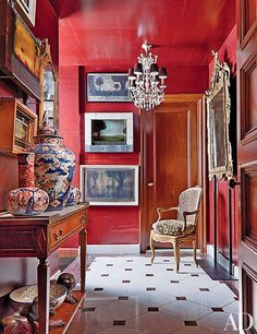 Seeing red? A ruby-tone Maya Romanoff wallpaper lines the walls and ceiling of this Manhattan apartment's hallway, which was decorated by John Yunis Ltd. — archdigest.com