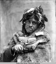 Portrait of man wearing fur cape and carved amulet necklace, holding raven rattle; [George Jim, Sr., of Angoon (1901-1997) identified this man as his paternal grandfather, Berner's Bay Jim (Aanxudaas, Dl'oogudzees), of the Wooshkeetaan clan of Toos' Hít (Shark House) of the Aak'w kwaan. His wife was L'ooknax.ádi and her name was Káaxáxweit;