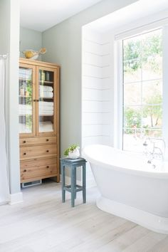 A BEAUTIFUL master bath with so many lovely touches! || Lake house master bathroom featuring Blustery Sky blue cabinets, white shiplap, and warm wood tones. A pedestal tub and chrome accents complete the look.