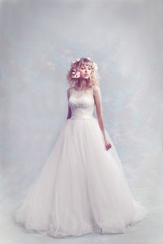 Embroidered illusion dotted tulle and re-embroidered lace bodice billowing elegantly into a full princess skirt. A perfect a-line silhouette finished immaculately with concealed zip. Available in ivory.