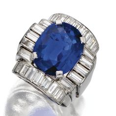 SAPPHIRE AND DIAMOND RING, VAN CLEEF & ARPELS, CIRCA 1935 The cushion-shaped sapphire weighing 10.04 carats, within a geometric frame set with 28 baguette diamonds weighing approximately 1.95 carats, mounted in platinum, size 5, signed Van Cleef & Arpels.