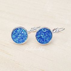 A pair of beautifully handcrafted druzy inspired earrings. Bright blue faux druzy stone cabochons are attached to silver plated lever back earring trays. These would be great for prom, or as wedding jewelry for brides, bridesmaids, flower girls, mother of the bride, etc... Also a great gift idea for Mother's Day, birthdays, anniversaries, Christmas, Easter, etc.... The blue is chic and classy, very stylish and fashionable for women, girls and teens. $13.99 a pair plus shipping.