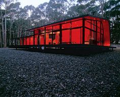 Fresh tomato sauce inspired the color used on this house in Australia. The red painted wall curves around and upwards to become the ceiling and roof of the unit.