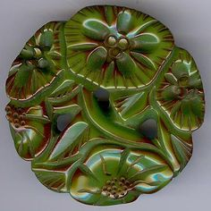 Carved FD flowers with etched like we coming in from edges. Green Bakelite button