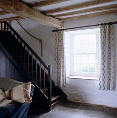 Above: A rustic wooden staircase leads upstairs from the living room. The original slate slabs have been scrubbed and sealed with linseed oil and turpentine.