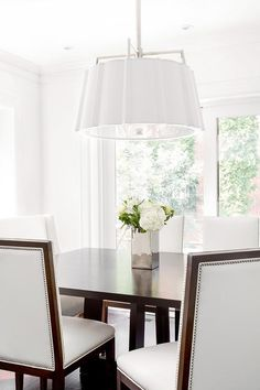 Beautifully designed elegant white and brown dining room features a white scalloped drum pendant, Hudson Valley Lighting Humphrey Pendant, hung above a brown rectangular dining table surrounded by white leather wingback nailhead dining chairs accented with a wood frame lit by natural light coming in from sliding glass patio doors. To see the whole family, visit: https://www.hudsonvalleylighting.com/Products/Family/humphrey