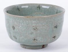 "A Korean Bowl, Celadon Glaze 18th century or earlier, with low circular foot, lobed body and repeated geometric decoration. 4 1/2"" d and 2 3/4"" tall"
