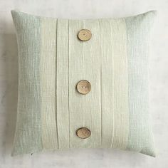 Our naturally charming pleated pillow combines a neutral panel accented with three dark wood buttons and bordered by a cool mineral hue. It's the perfect addition for looks from coastal to rustic and everything in between.