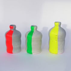 These beautiful matt grey earthenware bottles are traditionally made on the potters wheel. They are brought to life with the addition of some vibrantly coloured rubber! To protect your surfaces the base of the bottle is covered in dark pink flocking. Not food safe. Each bottle is unique but dimensions are approximately 12x6cm.
