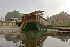 """The Butterfly Houseboat has a dining suite in mother of pearl … Before the political situation deteriated in 1989, many of the guests would stay for long periods of time and return frequently. Some of the guests gave presents to their hosts, including paintings and poetry. The bedrooms are themed, one bed is a lotus leaf, another a peacock, but the walkway is rotten and the western tourists no longer come."""