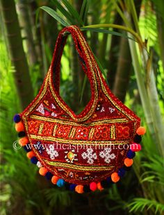 Kutch Embroidered Flower Pattern With Real Mirror Worked Banjara Bag Rs. 639 Our price is inclusive of GST taxes This Banjara bag is medium in size and is worked on both sides The thread work embroidery on only front side of the bag. This has multicolored pompoms all around the bags. Space is average space as the size of the bag. Dimensions: Length - 11 Inches Width - 13 Inches