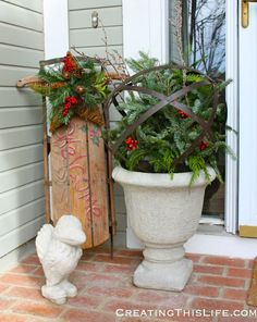 Porch decorated for Christmas with #urns, #sled, and #lantern.