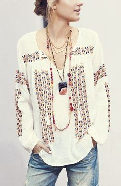 Embroidered peasant shirt, denim shorts, and layered necklaces