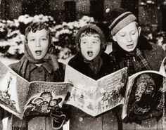Three young carol singers give their rendering of a Christmas song in the falling snow. (Photo by Keystone/Getty Images). 1957.