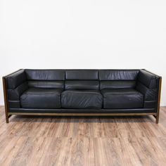 This mid century modern sofa is upholstered in a durable shiny black leather. This long sofa is in great condition with a low back, sleek tufted cushions and a simple wood frame. Comfortable and stylish couch perfect for a modern minimalist lounge! #midcenturymodern #sofas #sofaorcouch #sandiegovintage #vintagefurniture