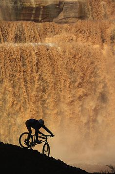 A mountain biker pedals past rushing winter snow melt at Grand Falls