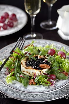 An elegant plate of Mixed Green Salad with Caramelized Goat Cheese, Red Grapes, and Pecans