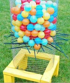 Outdoor Kerplunk game! Chicken wire, ball pit bals, wooden dowels on a wooden base. TOO CUTE!